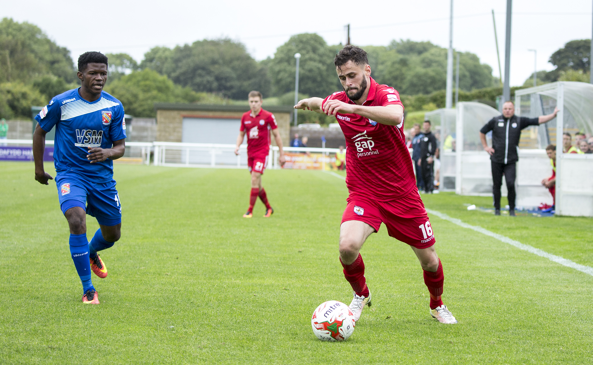 Nathan Woolfe takes on the Bangor City defence - © NCM Media