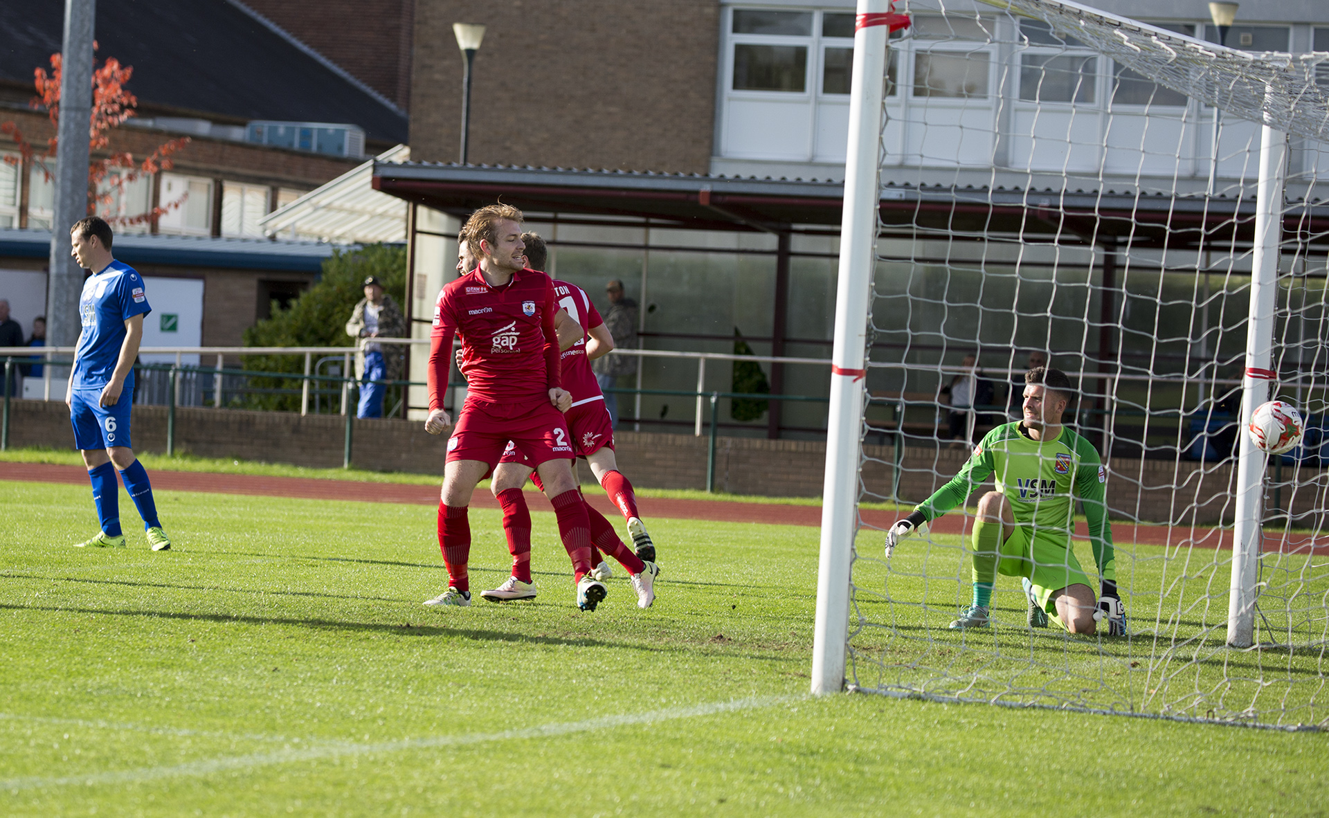 John Disney celebrates as River Humphreys' flick goes beyond Connor Roberts in the Bangor goal - © NCM Media