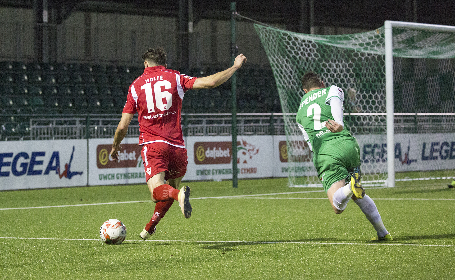 Nathan Woolfe bests Simon Spender to send a cross into the TNS box - © NCM Media