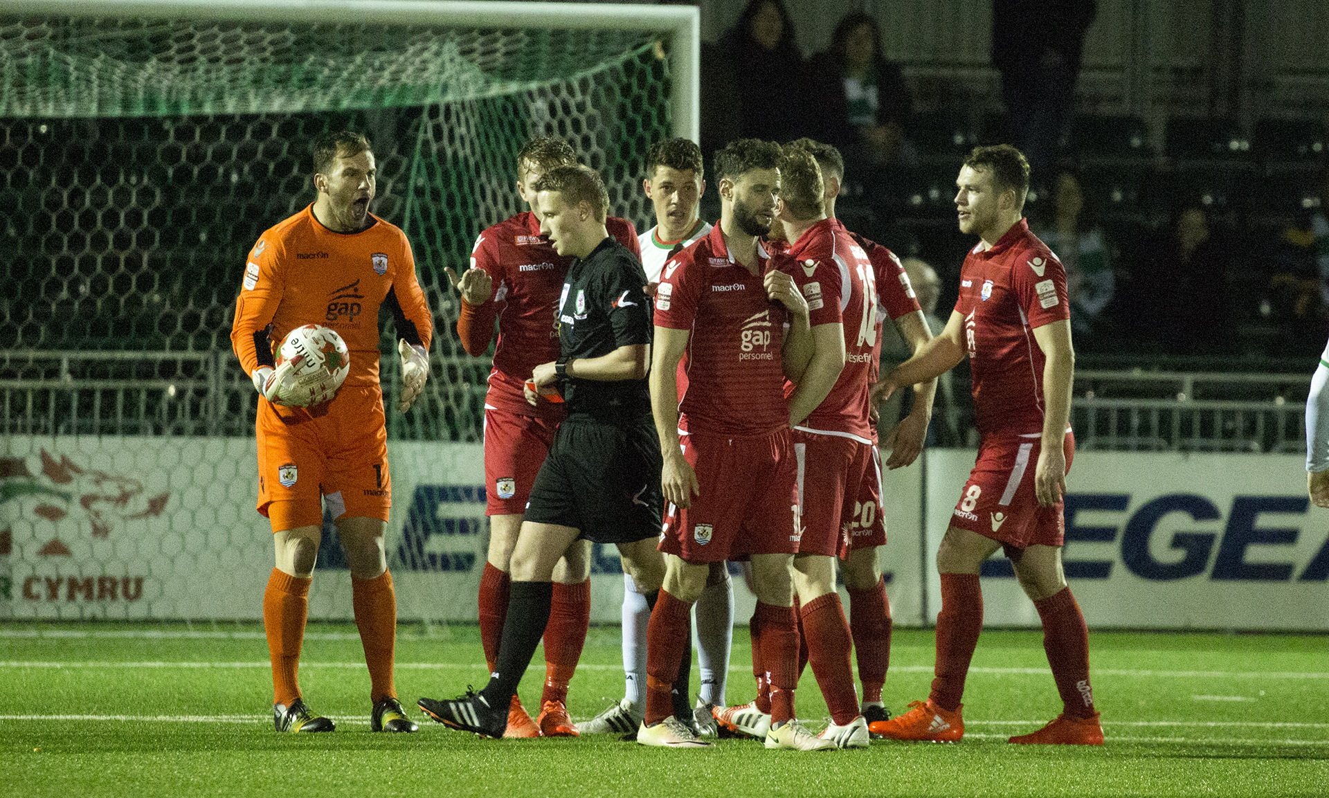 The Nomads' players react angrily as Nathan Woolfe is shown a straight red card