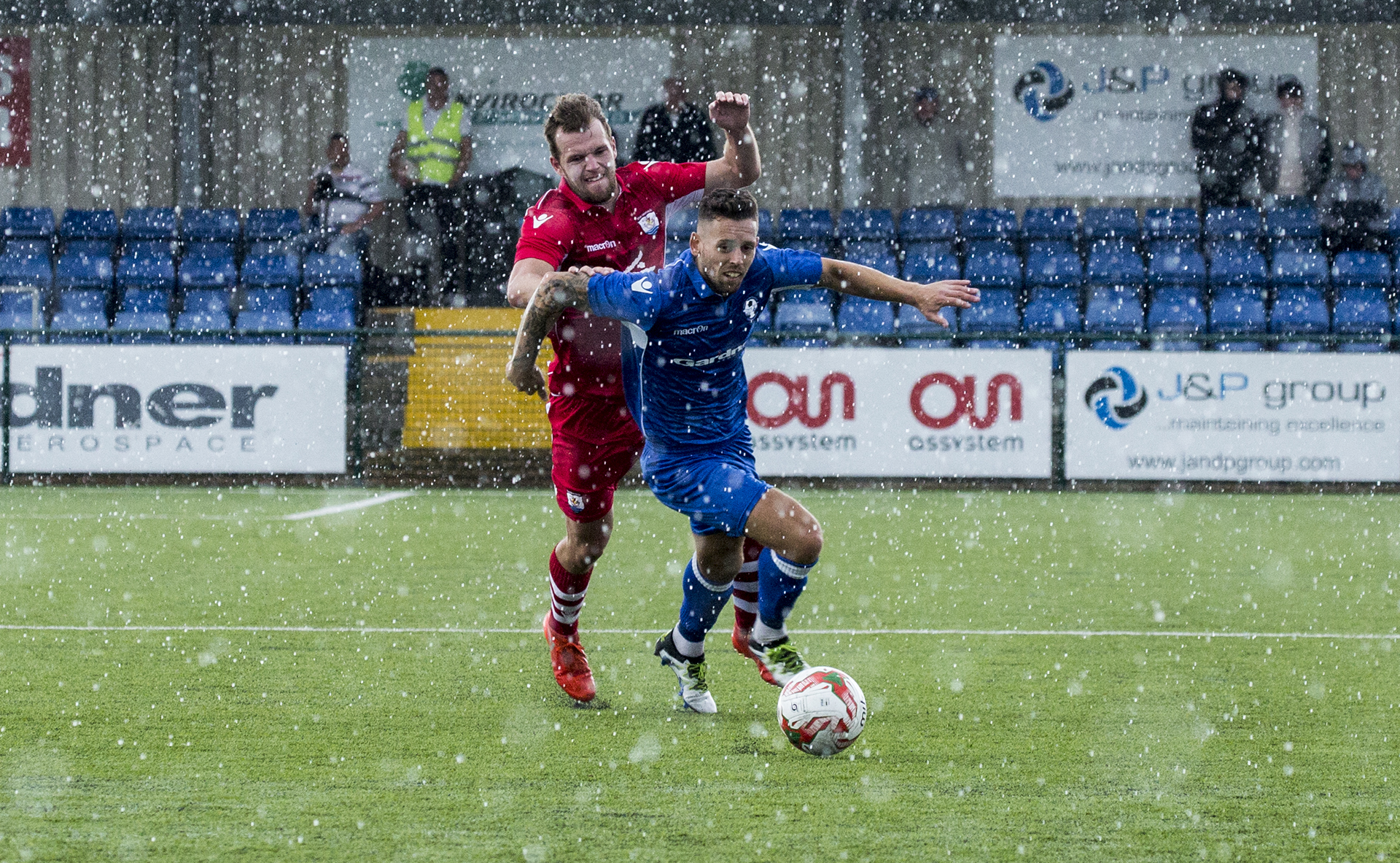 Ex-Nomads Wes Baynes and Callum Morris clash as they battle through the inclement weather - © NCM Media