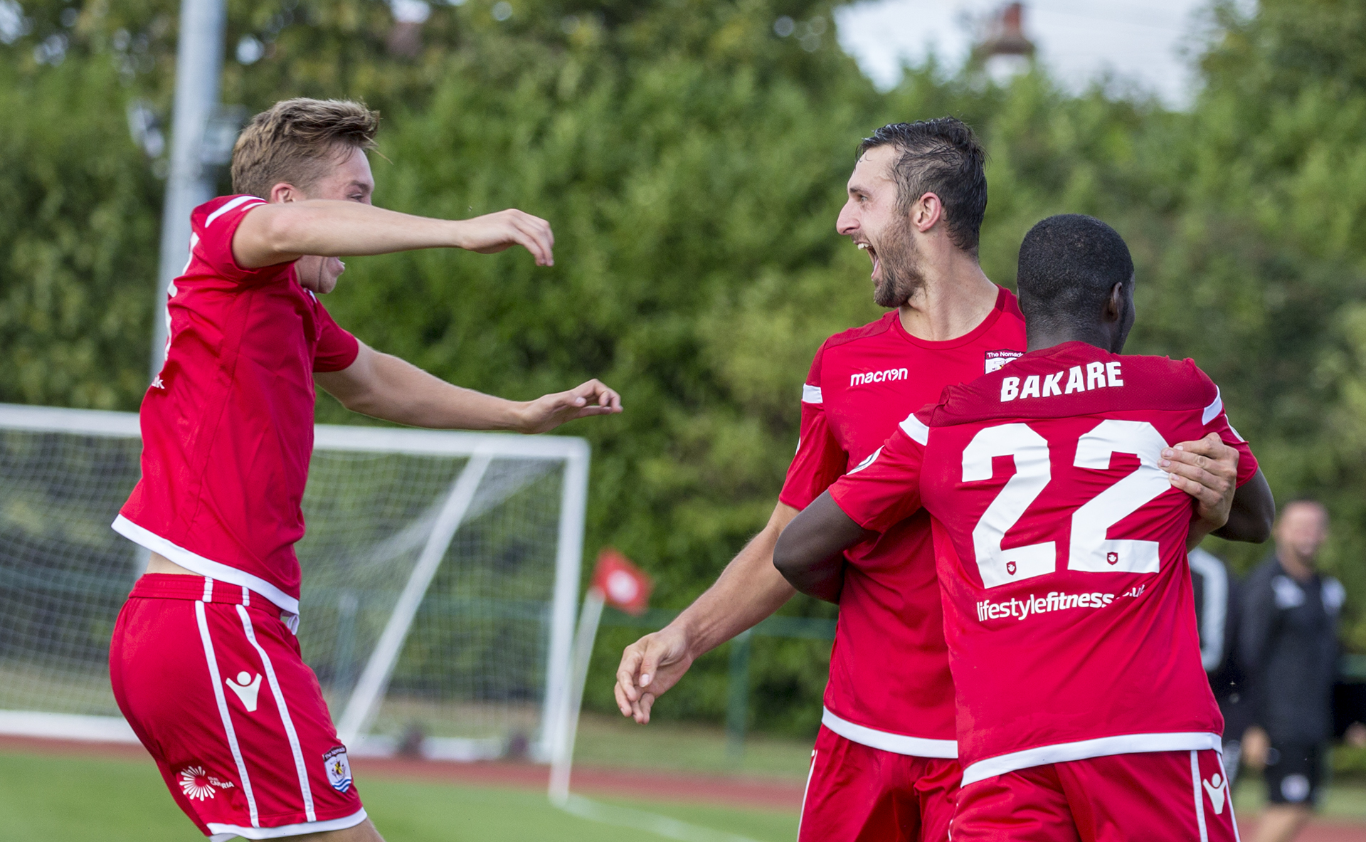 Andy Owens (centre) celebrates with Rob Hughes (left) and Michael Bakare (right) after his goal against TNS © NCM Media